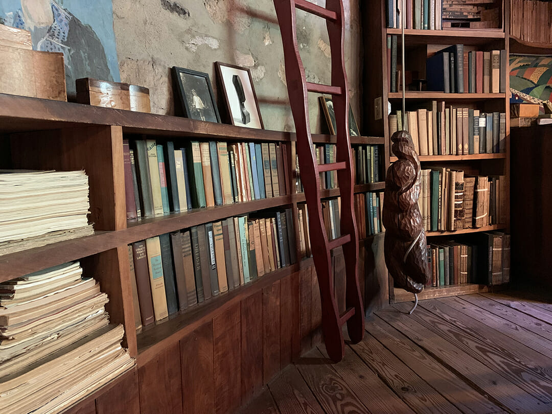 two rows of books to the left lead back to another vertical bookshelf. a red ladder leans in front of the two shelves and a carved wood sculpture hangs from a rope beyond the ladder. small items and photo lean against the wall above the bookshelves and the floor is pine wood boards.