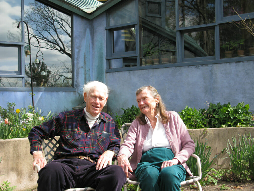 An elderly couple sit outside in front of a blue stucco building with large windows. The man is wearing corduroy slacks, a white turtleneck and a dark plaid shirt and smiling at the camera. The woman is wearing teal pants, and a pink cardigan over a collared shirt. She is turned toward the man and smiling