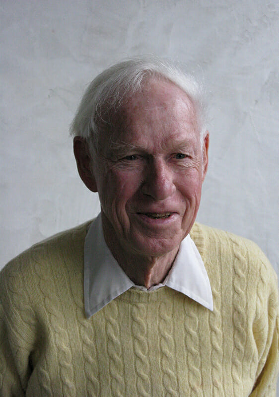 Elderly man with a collared shirt and pale yellow sweater and white hair is smiling and seated in front of a gray wall