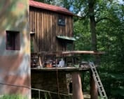 Image shows curving free-form deck on the Studio with grassy area in foreground and a colorful curving stucco wall to the left. A ladder leans up to the deck and tools are strewn about the deck.
