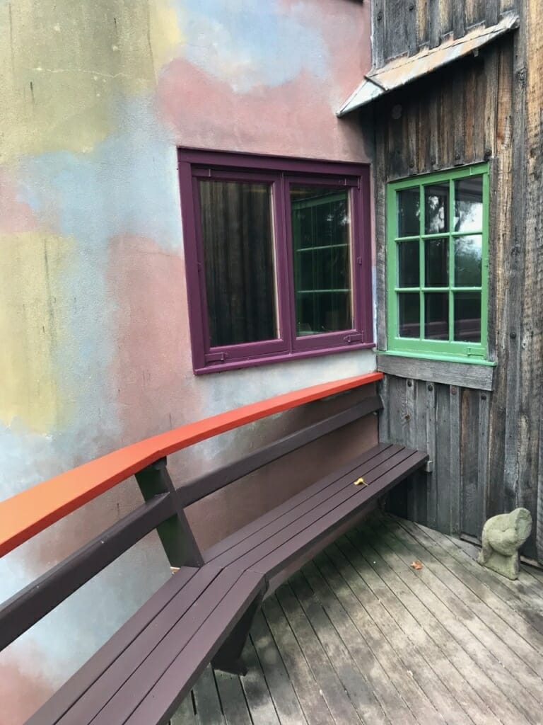 view of kitchen windows from the deck. Red railing and brown bench end in a corner with plum window on the left wall and green window on the right.