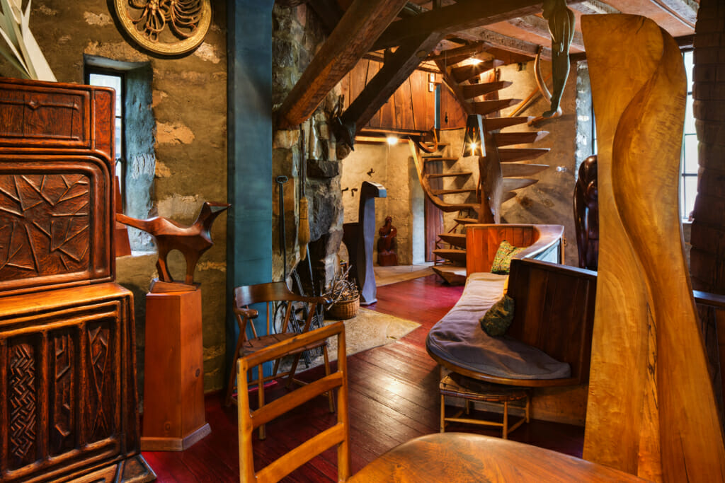 room full of handmade wooden furniture and sculpture, with handmade woden spiral staircase towards the far end of the room.