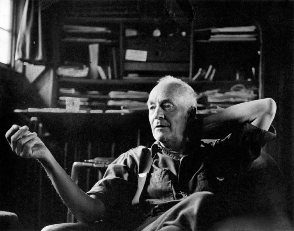 black and white photo of Wharton Esherick seated with his left hand behind his head and his right hand out in front of him, gesturing in conversation
