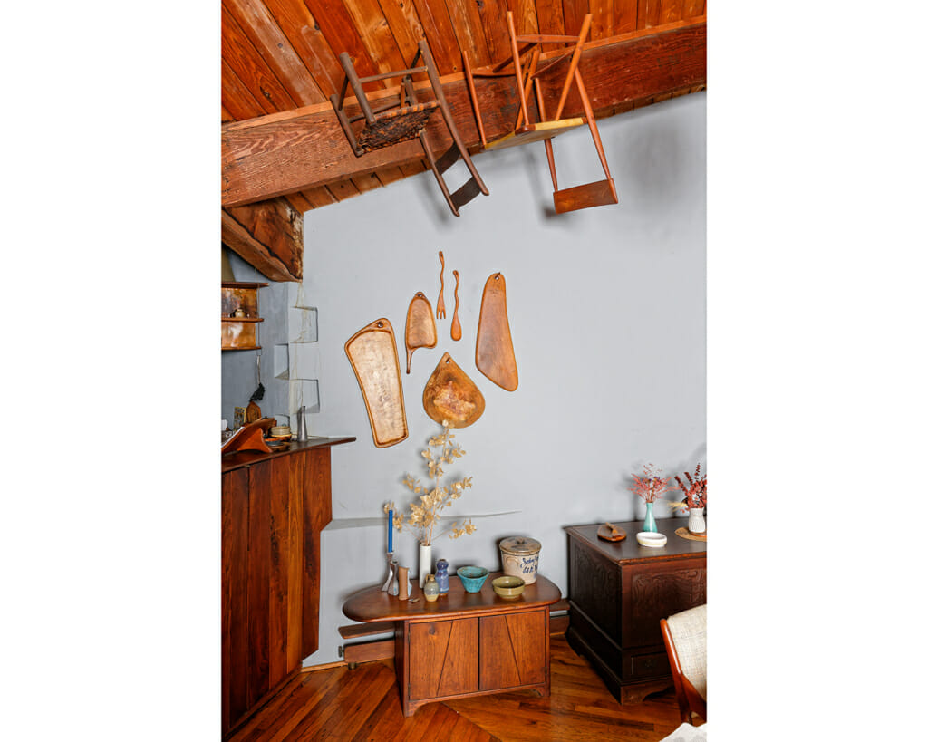 wooden platter and spoons hang on a wall over a wooden chest. Chairs hang from the ceiling.