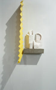 abstract ceramic white forms on a gray shelf next to a yellow vertical zig-zagging divider.
