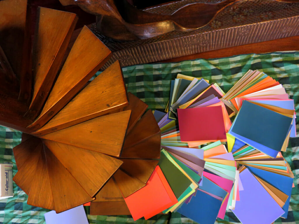 aerial view of wooden spiral staircase model and color-aid paper fanned out on a green tablecloth