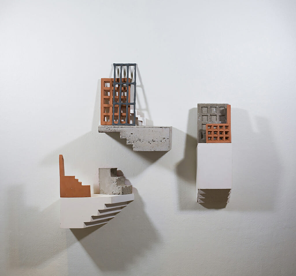 three sculptures on a white wall depict staircase and building like forms