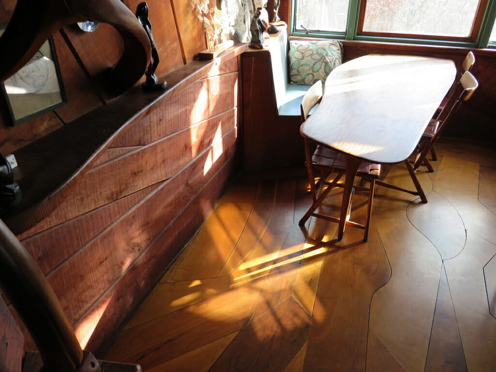 view looking down on wood floor, wall, and table with beams of light from the window pouring in