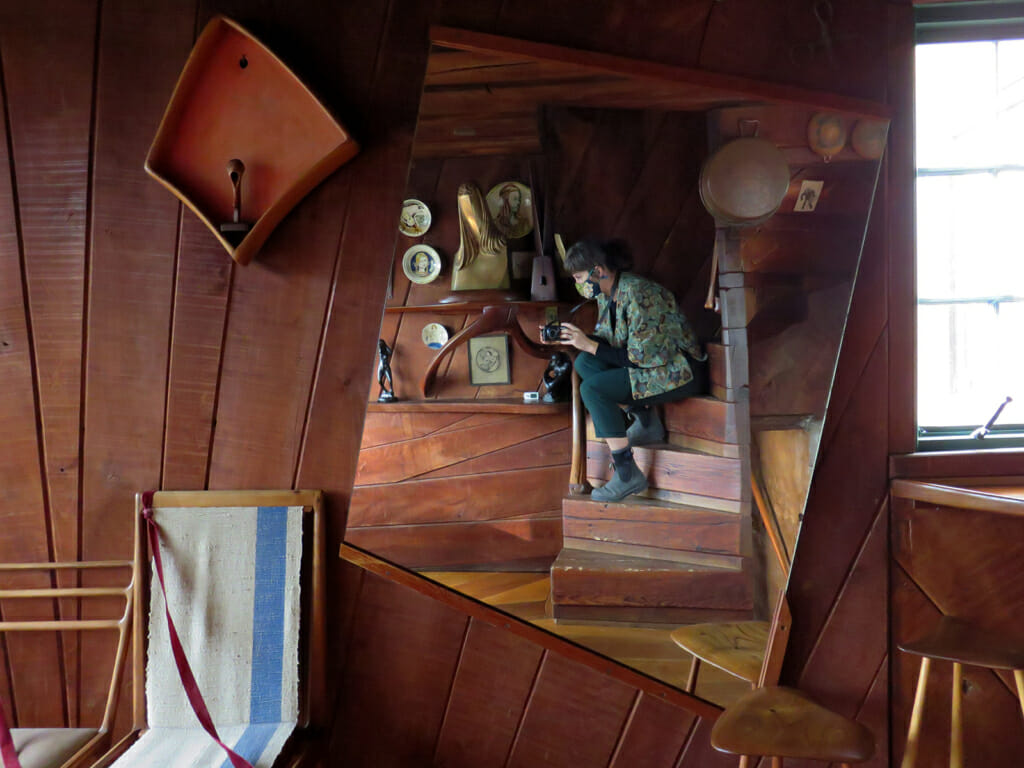 wood board wall with asymmetrical mirror on wall. In the reflection is a woman crouching on a wooden spiral staircase.