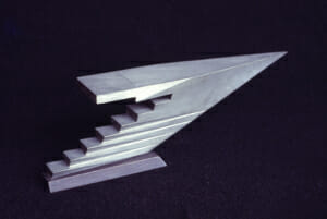 aluminum cast sculpture of an abstract pointed arrow form with step-like facets on the bottom