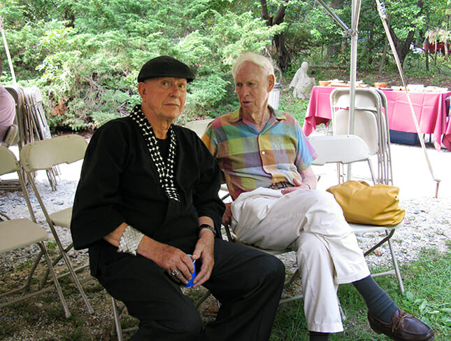 Two older men sit outside on folding chairs. One wears all black, with a black cap, and silver armband. The other wears white slacks and a pastel plaid button-down shirt.