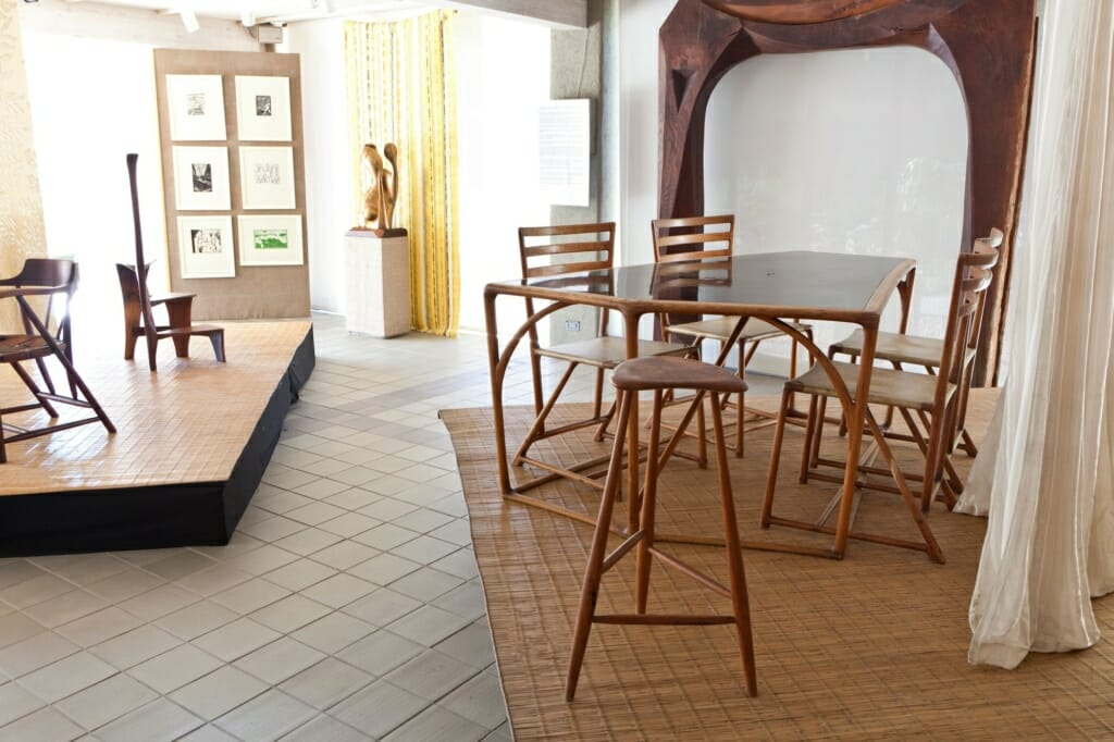Installation view of gallery displaying tables, chairs and stools by Esherick with fabric dividers and backdrops. A large wood archway stands at the back wall.