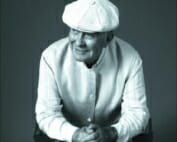 a older man in a white cap and white shirt leans forward, resting on his elbows with his hands held together. He looks off to his right slightly and has a friendly gentle smile.