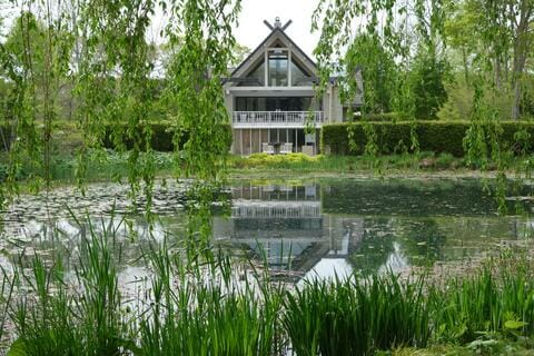 An a-frame house sits across a pond. There are hanging green tree limbs, green grasses, lilypads, and a hedge around the pond.