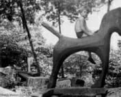 black and white photo of boy on wooden horse sculpture.