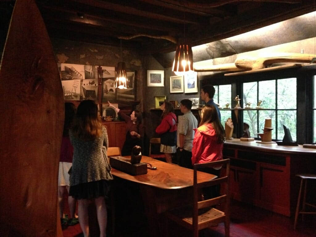 a tour guide point to a photograph inside the Esherick Studio, surrounded by students