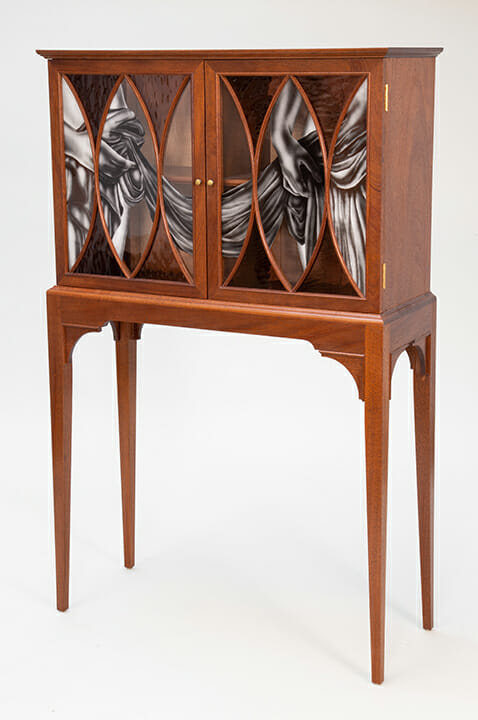 Glass front cabinet on four tall legs. On glass the waistlines, with hands, of two figures, a male and female, are etched