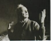 old man wearing shirt and cardigan gestures with one hand up and the other behind his back