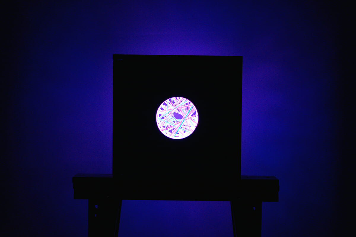 dark room with a box in the middle with a cut out circle and glowing light inside