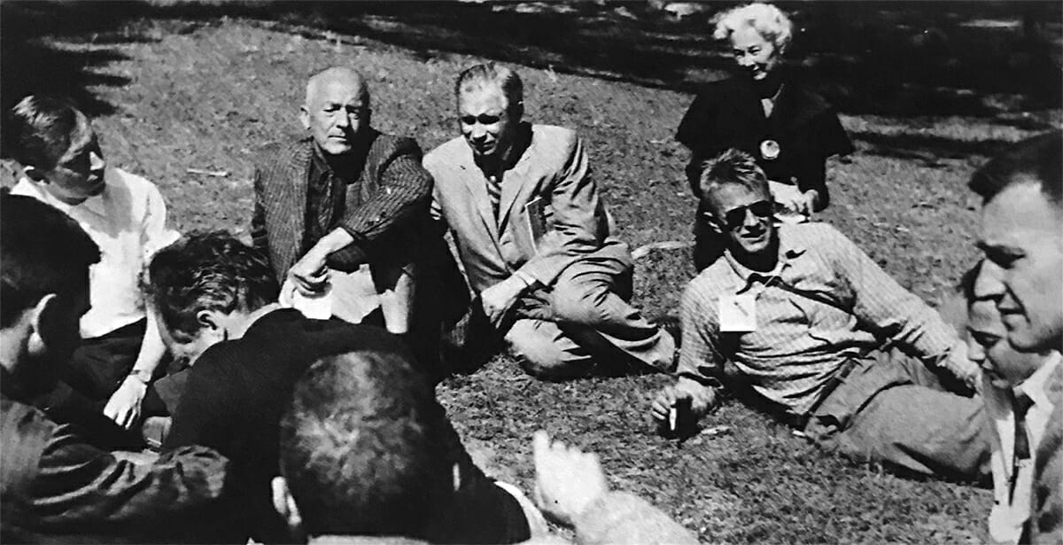 black and white photo of group of people sitting in the grass
