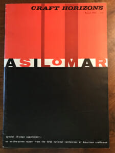 """booklet lays on a wooden desktop. It has a bold cover design with solid red and black color fields and say """"Asilomar"""" across the center."""