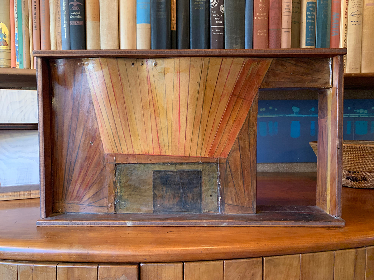wood and paper model of a fireplace sits on a cabinet in front of a shelf of books