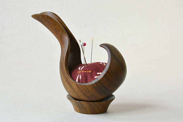 curving wood scoop form with fabric inside making a pincushion