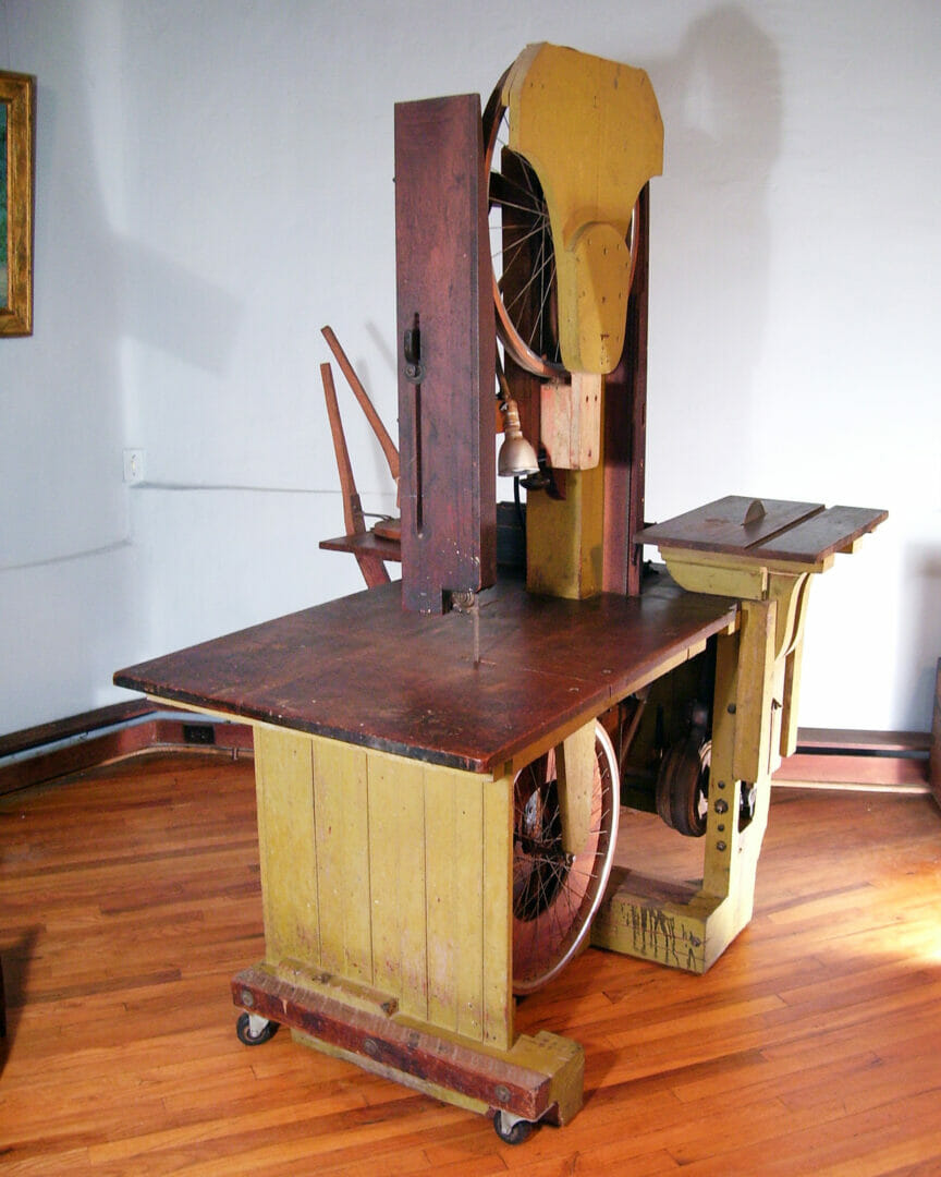 a homemade bandsaw made of wood and bicycle wheels sits in a room with a wood floor and pale lavender walls. The table surface of the bandsaw is a dark wood and the vertical sides of the tool are painted a mustard yellow.