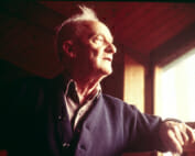 Wharton Esherick when he is older looks thoughtfully out a window as afternoon light illuminates his face. He leans his arm on the windowsill and is wearing a collared shirt and a dark blue cardigan.