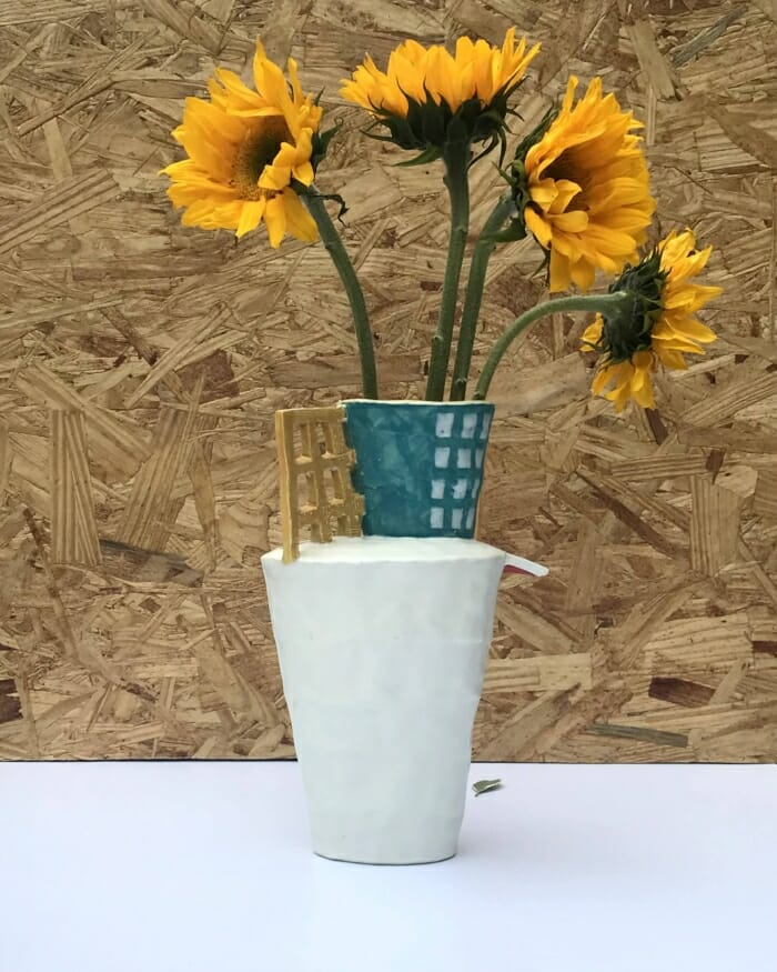 tall and narrow ceramic vase with yellow grid and turquoise top, holding yellow sunflowers