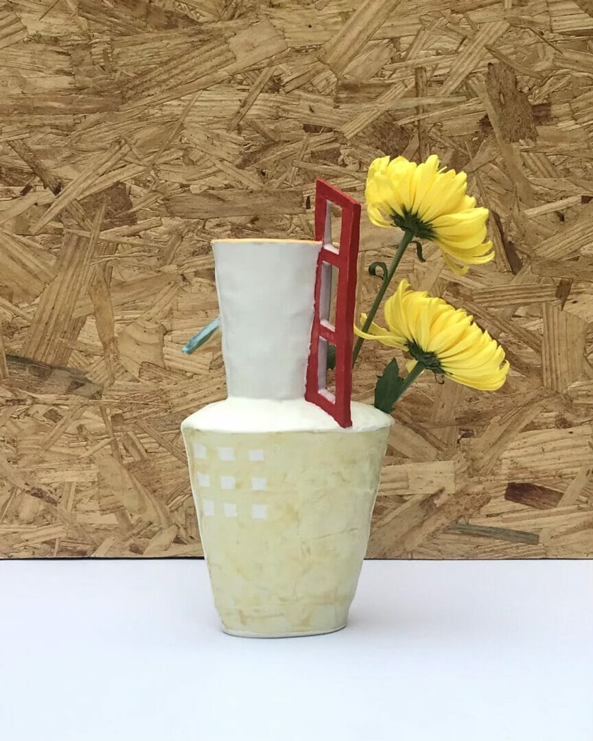 """tall white ceramic vessel with turquoise """"awning"""" feature and tall three pane red window. Back side has faint yellow grid on surface"""