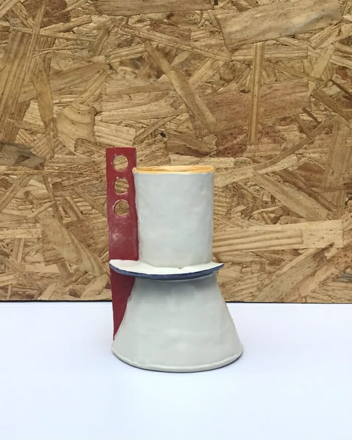 small vessel with yellow base and interior with red flange with three holes