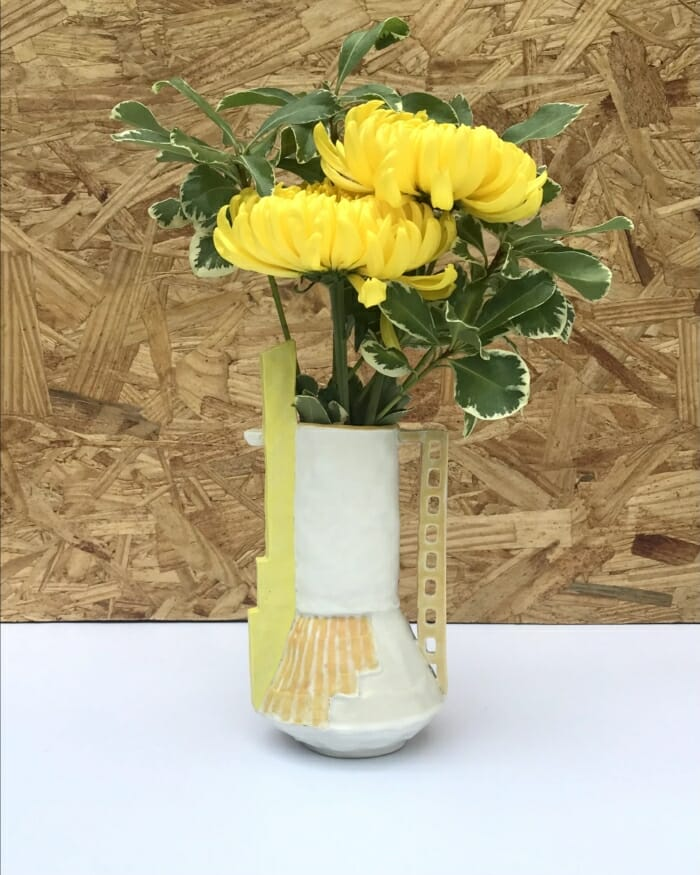 """small vase with painted orange lines, tall yellow """"chimney"""" and ladder-like handle"""