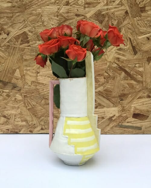 """small vase with painted yellow lines, tall yellow """"chimney"""" and pale reddish pink ladder-like handle"""