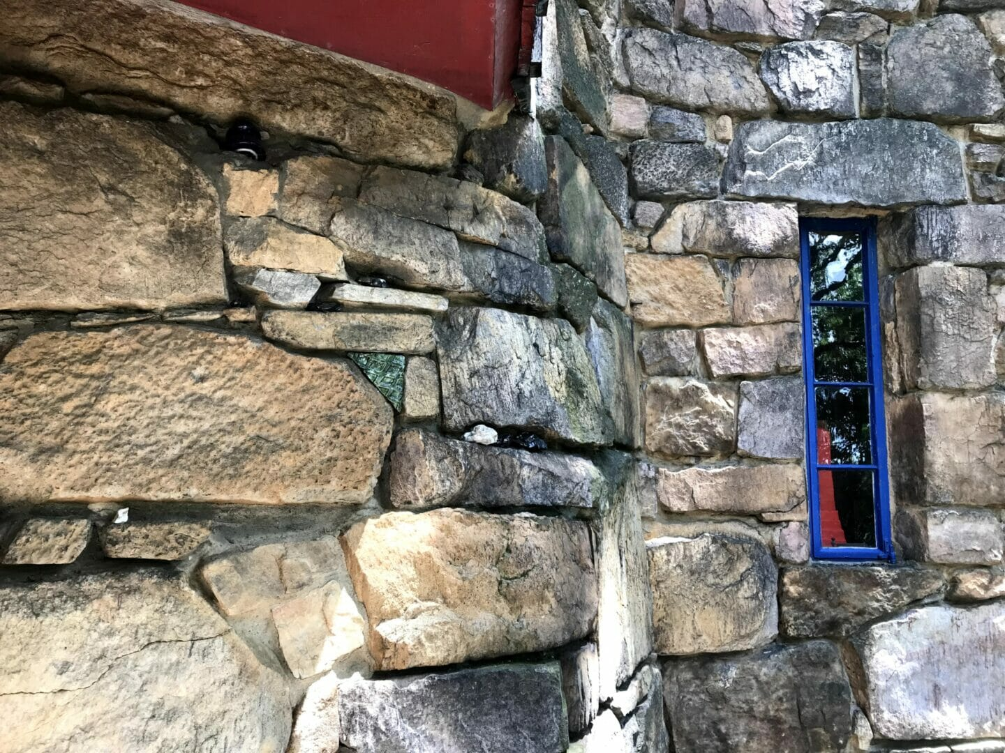 A stone wall with a tall narrow, blue window towards the right. In the window we can see a bright red abstract sculpture.