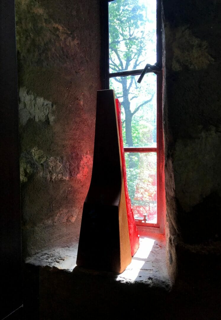 A red sculpture can be seen behind one of Esherick's wood sculptures. Both sit on the sill of a tall, narrow stone window and a red glow reflects around the sculptures.