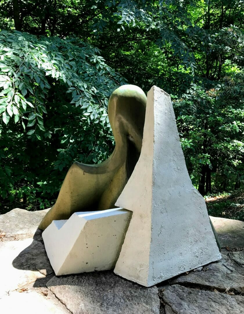 a bronze pelican sculpture is partially obscured by angular white forms. They sit on a stone patio with green woods in the background.
