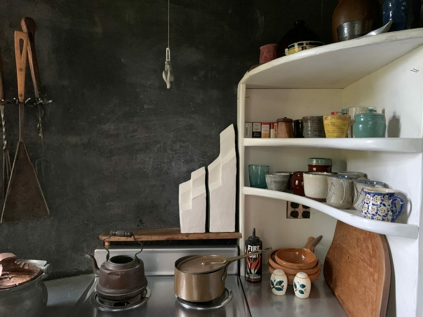 two stepped white sculptural forms sit on a shelf behind a kitchen stove. White shelves with kitchen items extend to the right.
