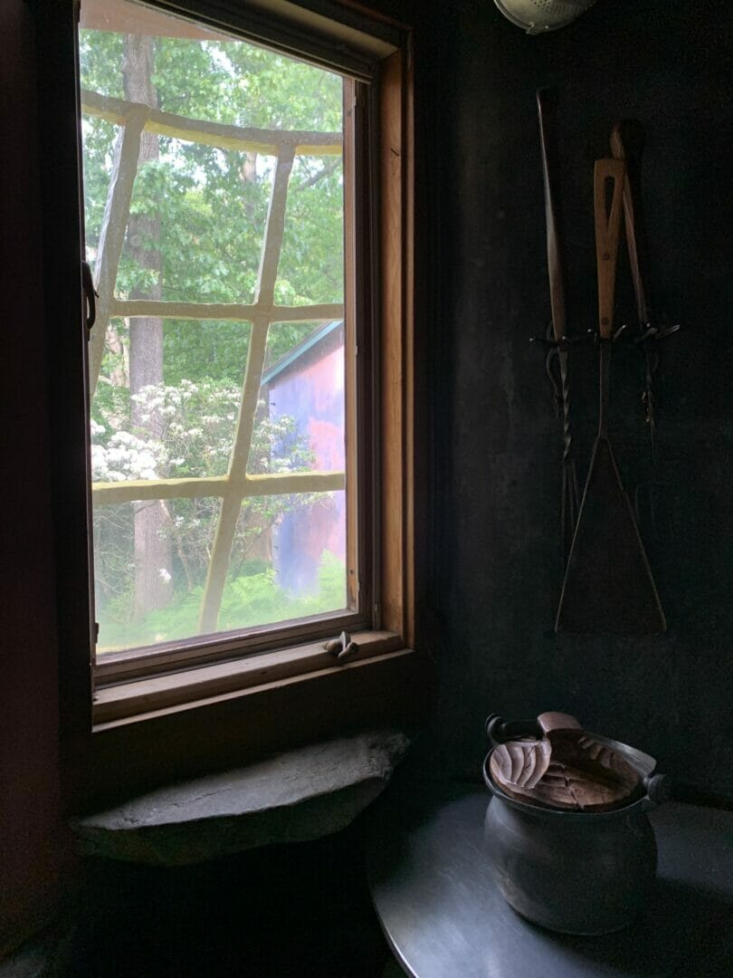 The view from inside the kitchen window shows the grid and a metal pot with a carved wooden lid on a counter in the bottom right of the frame.