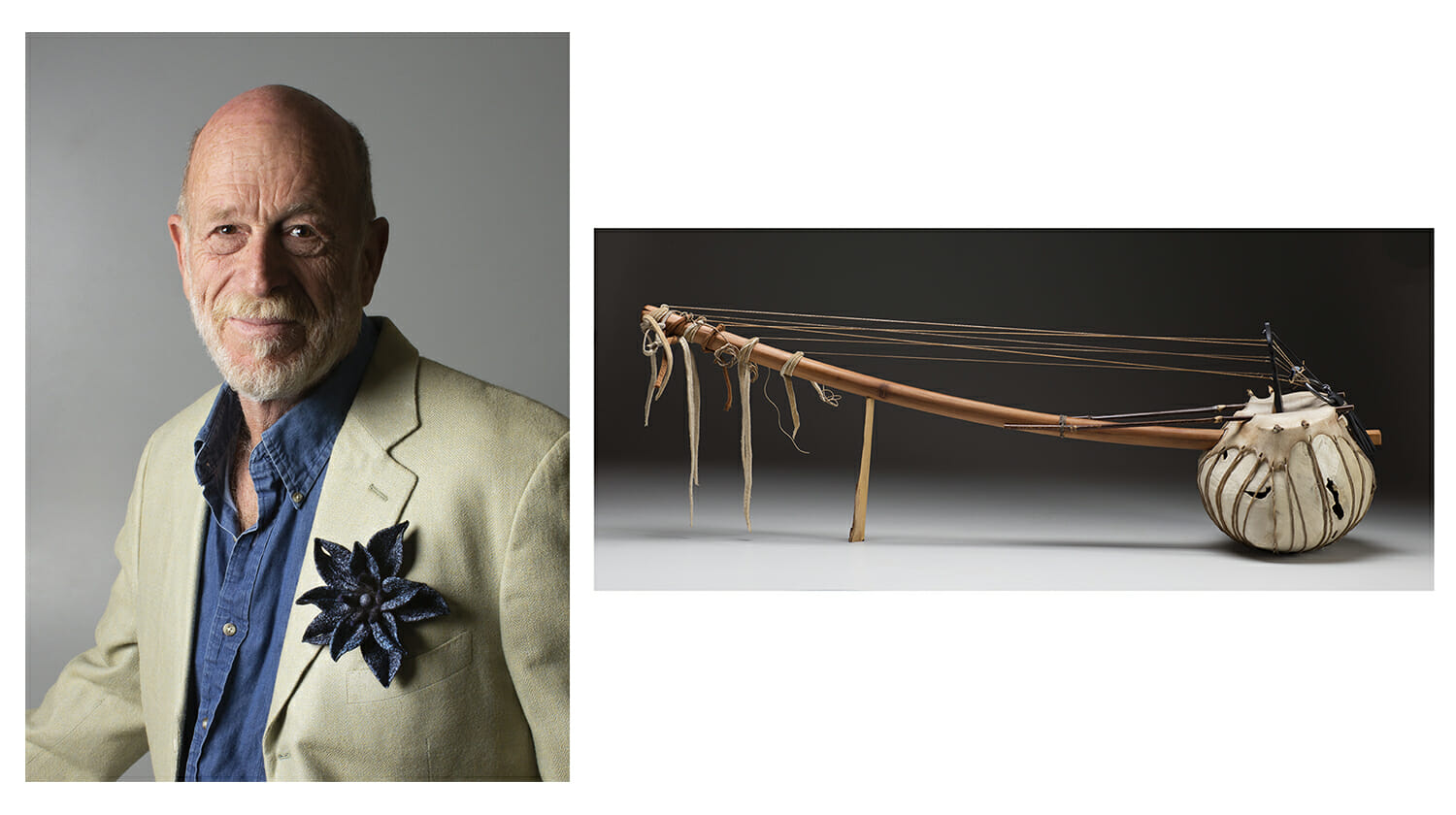 On the left is a man with a blue collared shirt and light cream blazer with a large blue floral pin on his jacket. he is bald with a short white beard. on the right is a handmade stringed instrument with a round body, long neck and leather hanging from the end.