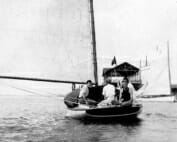 black and white photo of a young Wharton sitting on the back of a sailboat, and facing the viewer. His brothers are also on the boat, which is moving away from us.