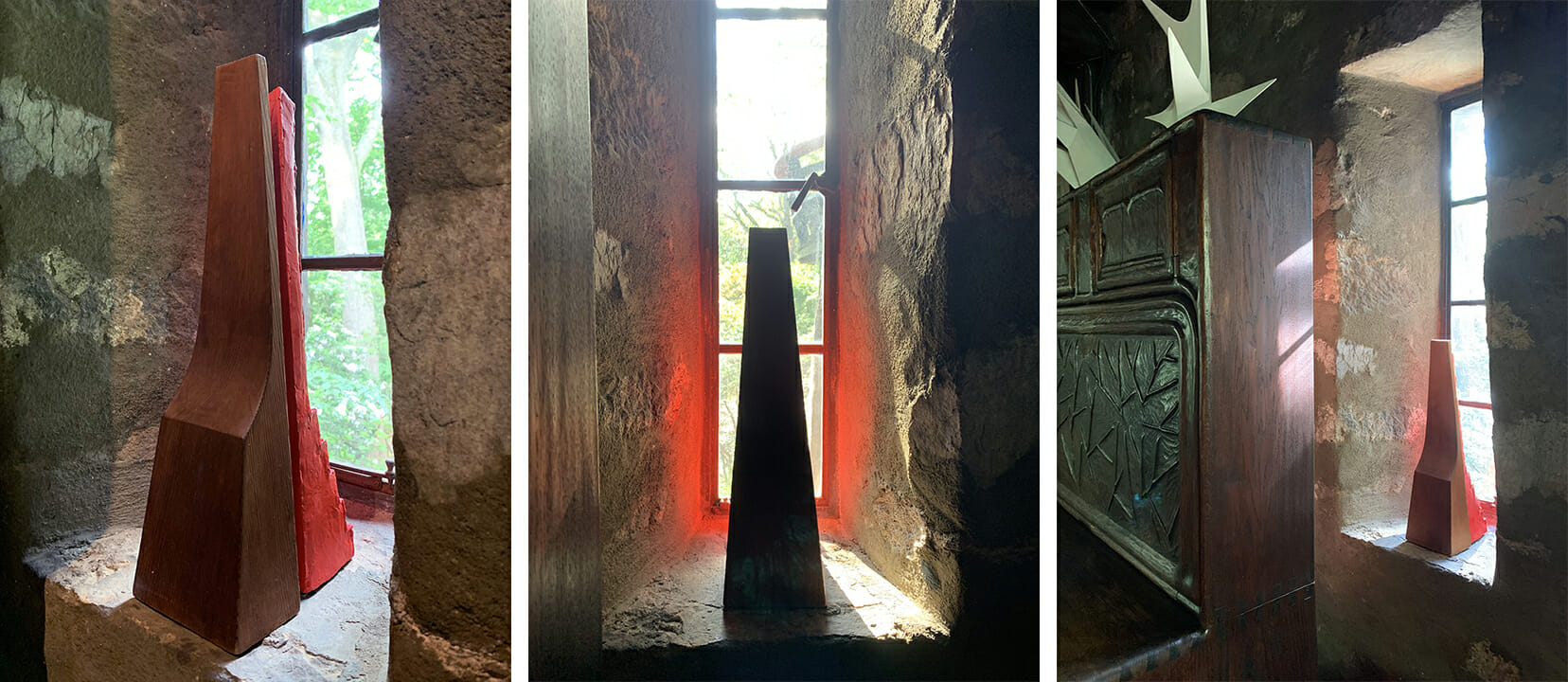 Three views of a deeply recessed window with a pine sculpture with a red sculpture behind it which casts red reflections onto the stone wall.