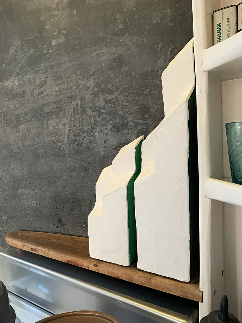 two abstract white sculptures on a wood shelf in esherick's kitchen. There is a sliver of green seen between the two forms.